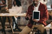 oříznutý pohled úsměvu afroamerické příležitostné podnikatel hospodářství tablet s prázdnou obrazovkou a kolegy pracující v podkroví úřadu za
