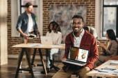 Fotografie African american casual Geschäftsmann hält Laptop mit Online-Karten-Web-Site und Kollegen hinter Loftbüro