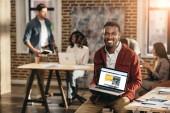 africké americké neformální podnikatel drží notebook s rezervační web a kolegy pracující v podkroví úřadu za