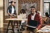 africké americké neformální podnikatel drží notebook s prázdnou obrazovkou a kolegy pracující v podkroví úřadu za