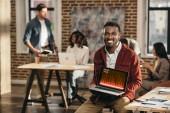 African american casual Geschäftsmann hält Laptop mit Graph auf Bildschirm und Kollegen hinter Loftbüro