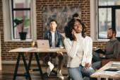Veselá africká americká příležitostné podnikatelka sedí a mluví na smartphone v podkroví úřadu s kolegy pracující za
