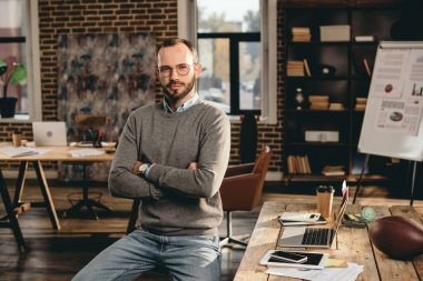 serious casual businessman sitting at desk with arms crossed in loft office