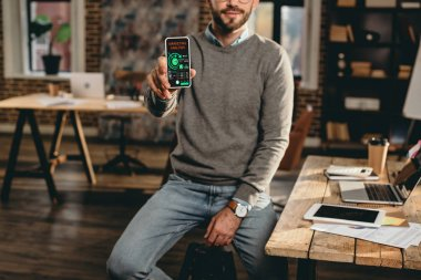 cropped view of casual businessman holding smartphone with marketing analisys app on screen in loft office