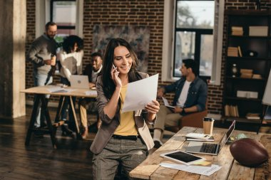 casual businesswoman working and talking on smartphone in loft office with colleagues behind