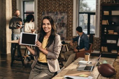 casual businesswoman holding tablet with blank screen in loft office with colleagues working behind