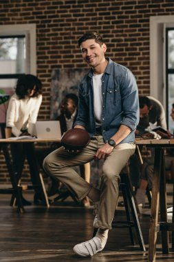 smiling young man holding rugby ball in modern loft office wiith colleagues on background