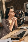 pensive business woman sitting at desk with laptop and working at loft office with colleagues on background