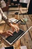 oříznutý pohled ženských rukou, psaní na notebooku u stolu s kancelářské potřeby