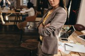 cropped view of business woman standing at desk in loft office with colleagues on background