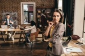pensive business woman standing at desk with laptop at loft office with colleagues on background
