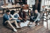 középpontjában a többnemzetiségű csoport a padlón ül, és megvitassa együtt új projekt a modern loft office colworkers