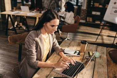 stressed business woman sitting at desk with laptop and working at loft office with colleagues on background