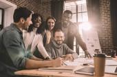 s úsměvem mnohonárodnostní skupiny kolegy spolupracovat na novém projektu v moderní podkrovní kanceláře s podsvícením