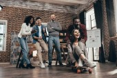 Photo cheerful group of multiethnic coworkers having fun with skateboard in loft office