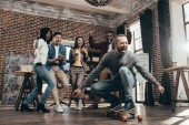 Photo group of multiethnic coworkers having fun with skateboard in loft office