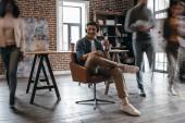 příležitostné podnikatel v heaphones sedí na židli s kolegy v pohybu rozostření v kanceláři moderní loft