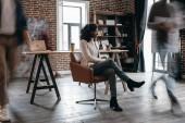 africká americká podnikatelka v heaphones sedí na židli s kolegy v pohybu rozostření v kanceláři moderní loft
