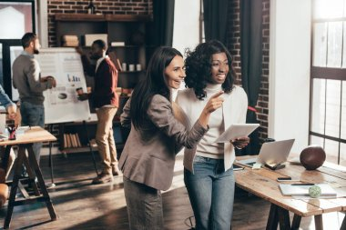 multiethnic couple of business women smiling and working in loft office with colleagues on background