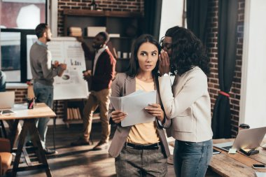 multiethnic couple of business women whispering in loft office with colleagues on background
