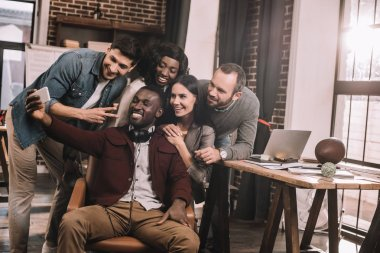 group of cheerful multiethnic coworkers taking selfie using smartphone in loft office with backlit
