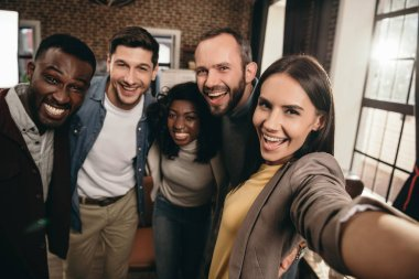 camera point of view of group of cheerful coworkers taking selfie using smartphone