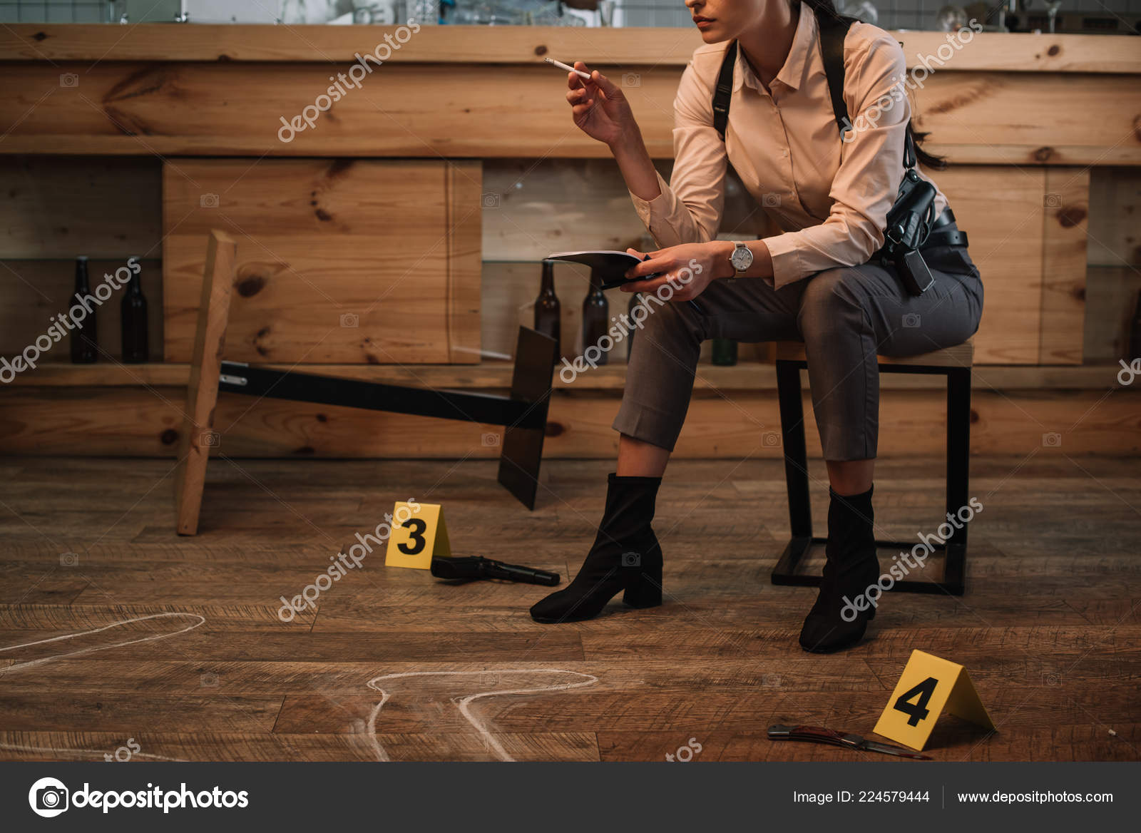 Cropped View Of Smoking Female Detective Sitting At Crime Scene With Evidence Markers And Dead Body Outline Photo By VitalikRadko