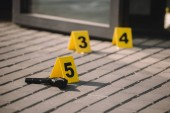 Photo close up view of crime scene with gun and numbers