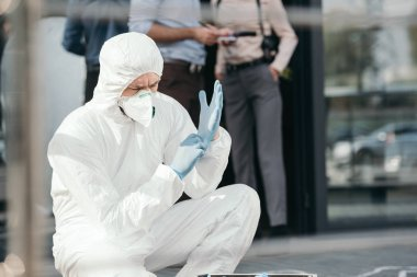 male criminologist in protective wearing latex gloves with cropped detectives behind