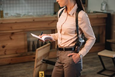 cropped view of female detective collecting data and investigating crime scene
