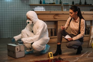 forensic investigator and focused female detective taking notes and examining crime scene together