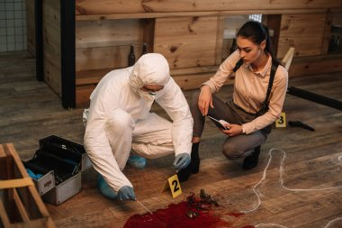 forensic investigator and female detective taking notes and examining crime scene together