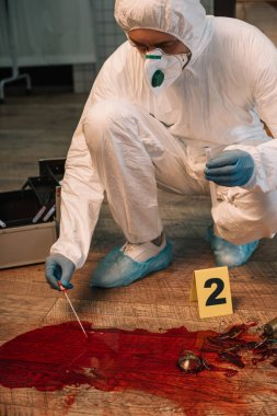 cropped view of forensic investigator in latex gloves taking blood samples at crime scene