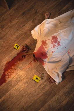 top view of dead body covered with white sheet at crime scene