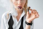 Fotografie abgeschnittene Ansicht des modischen blonden Mädchens, das Zigarre auf Grau raucht