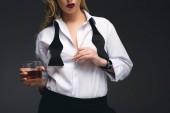 oříznutý pohled stylová holka ve formální oblečení drží sklenku koňaku, izolované na tmavě šedá