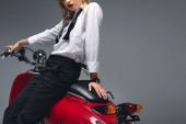 oříznutý pohled stylové elegantní dívka pózuje na červený skútr izolované Grey