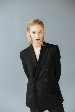 young stylish woman posing in black suit isolated on grey