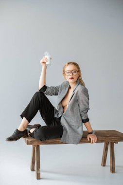 fashionable girl holding glass of milk and sitting on wooden bench on grey