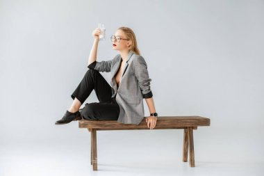 stylish girl holding glass of milk and sitting on wooden bench on grey