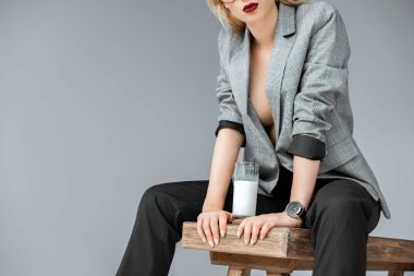 cropped view of fashionable woman sitting on wooden bench with glass of milk isolated on grey