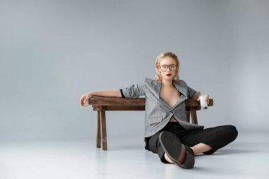 stylish girl holding glass of milk and sitting near wooden bench on grey