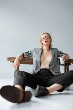 fashionable half nude young woman with glass of milk and sitting near wooden bench on grey