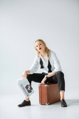 attractive fashionable girl holding business newspaper while sitting on vintage suitcase on grey