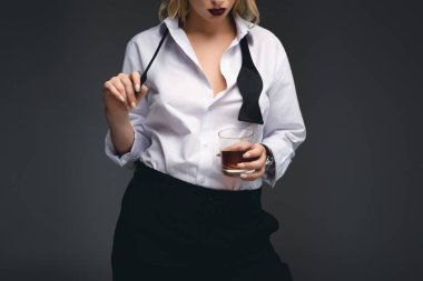 cropped view of elegant girl in stylish formal wear holding glass of whiskey, isolated on dark grey