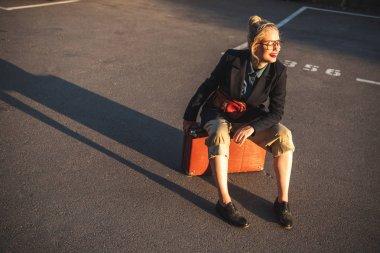 fashionable smiling girl sitting on retro suitcase on urban parking