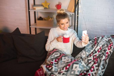 Young happy blonde woman covered in blanket sitting on couch, holding cup of hot cocoa with marshmallows and taking selfie on smartphone at christmas time stock vector