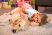 Fotografia bella giovane donna bionda sdraiato sul pavimento e che abbraccia cane golden retriever a casa il soffice tappeto a tempo di Natale