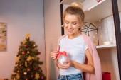 mosolygó fiatal szőke nő gazdaság gyertya piros szalaggal karácsonykor