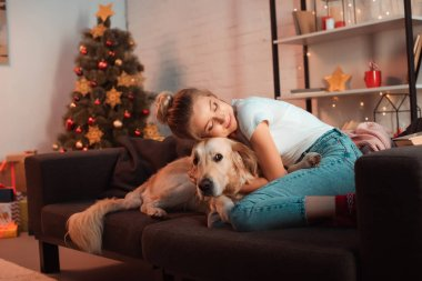 beautiful content young blonde woman on couch hugging golden retriever dog at christmas time